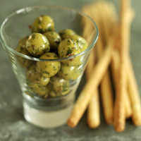 Popular : Close up of some breadsticks and a small glass of olives