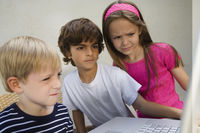 Concerned kids looking at a laptop