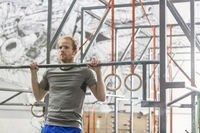 Confident man doing chin-ups in crossfit gym