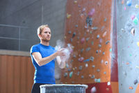 Popular : Confident man dusting powder by climbing wall in crossfit gym