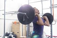 Confident man lifting barbell in crossfit gym