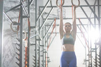Confident woman exercising with gymnastic rings in crossfit gym