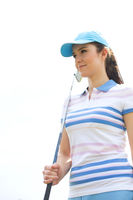 Popular : Confident woman looking away while holding golf club against clear sky
