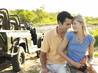 Couple embracing outdoors looking in eyes jeep in background