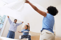 Couple holding bed sheet over son  3-6