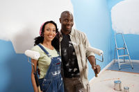 Couple holding paint rollers portrait elevated view