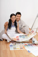 Couple looking at paint colour samples sitting on floor portrait