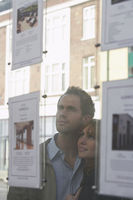 Couple looking through window at estate agents