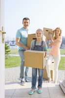 Family with cardboard boxes entering new house