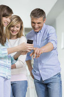 Father and daughters using smart phone at home