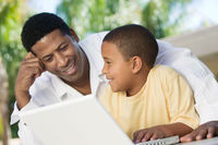 Father and son sitting on patio using laptop close up
