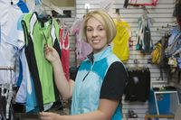 Female cyclist in bike shop choosing cycling top