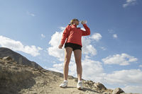 Female jogger drinking from water bottle in mountains