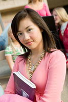 Female student holding book outdoors  portrait