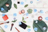 Flatlay of makeup accessories and plants