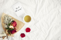 Flatlay of white cloth background with bouquet of roses