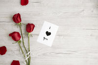 Flatlay of wooden background with rose and romantic message
