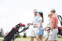 Popular : Friends communicating while walking at golf course against clear sky