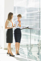Full-length of businesswomen discussing over tablet pc while standing by railing in office