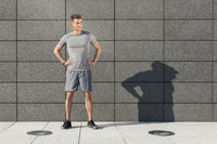 Popular : Full length of determined jogger standing against tiled wall outdoors