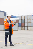 Full-length of female engineer using tablet computer in shipping yard