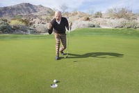 Popular : Full length of senior male golfer celebrating sinking putt at golf course