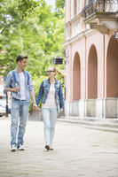 Full length of young college couple talking while walking in campus