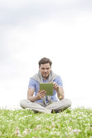 Full length of young man using digital tablet while sitting on grass against sky