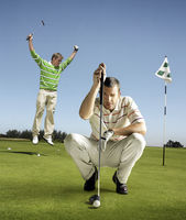 Popular : Full length portrait of golfer lining up shot with man jumping in background