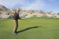 Popular : Full length side view of senior male golfer swinging his club at golf course