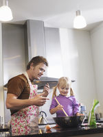 Girl  3-4  and father baking in kitchen