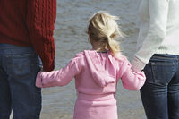 Girl  5-6  holding hands with parents at ocean