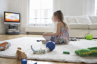 Girl  5-6  sitting on floor surrounded with toys watching television