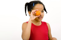 Girl covering her eye with an orange