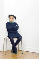Girl folding her arms while sitting on chair