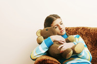 Girl hugging her teddy bear while sleeping on the couch