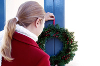 Girl putting up a wreath on the door