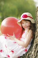 Girl with red ball  leaning against tree