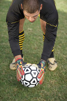 Goalkeeper bending down with ball portrait