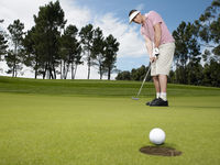 Popular : Golfer putting low angle view