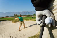 Popular : Golfer watching other golfer hit ball from sand trap
