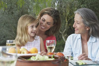 Grandmother mother and daughter  5-6  sitting at table in garden