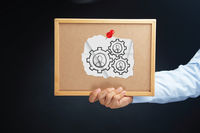Hand holding a board with cogwheels concept