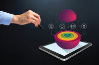 Hand holding a digital pen with layered sphere chart on digital tablet