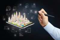Hand holding a digital pen with tablet and city concept