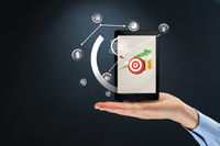 Hand presenting business target icons on tablet pc concept
