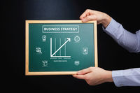 Hands holding blackboard with business strategy concept