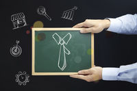Hands holding blackboard with necktie