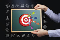 Hands holding chalkboard with business target concept