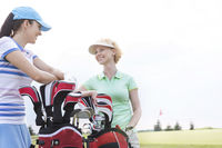 Popular : Happy female golfers talking at golf course against clear sky